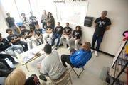 Wayne Lewis (center, in blue) speaks with kids in October 2018.