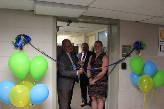 From left to right: Kevin Keeler, Amy Dorr, John Patterson, and a representative from Lansing Mayor, Andy Schor's office, cutting the ribbon on the new NAMI Lansing office space.