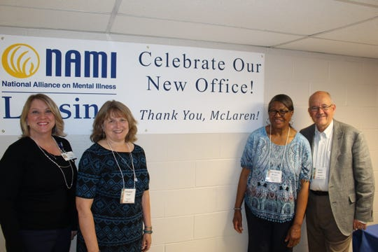 From left to right: Amy Dorr, Elizabeth Pratt, Jerri Nicole Wright, and Kevin Keeler, posing in front of the celebratory banner