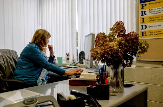Julie Taylor, principal of Hayes Middle School in Grand Ledge, works on her computer Monday, Oct. 15, 2018. Taylor received a stem cell transplant at the end of January, and is recovering.