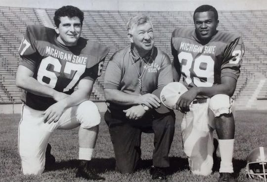 MSU Coach Duffy Daugherty with co-captains Tony Conti, left, and Drake Garrett, undated photo.