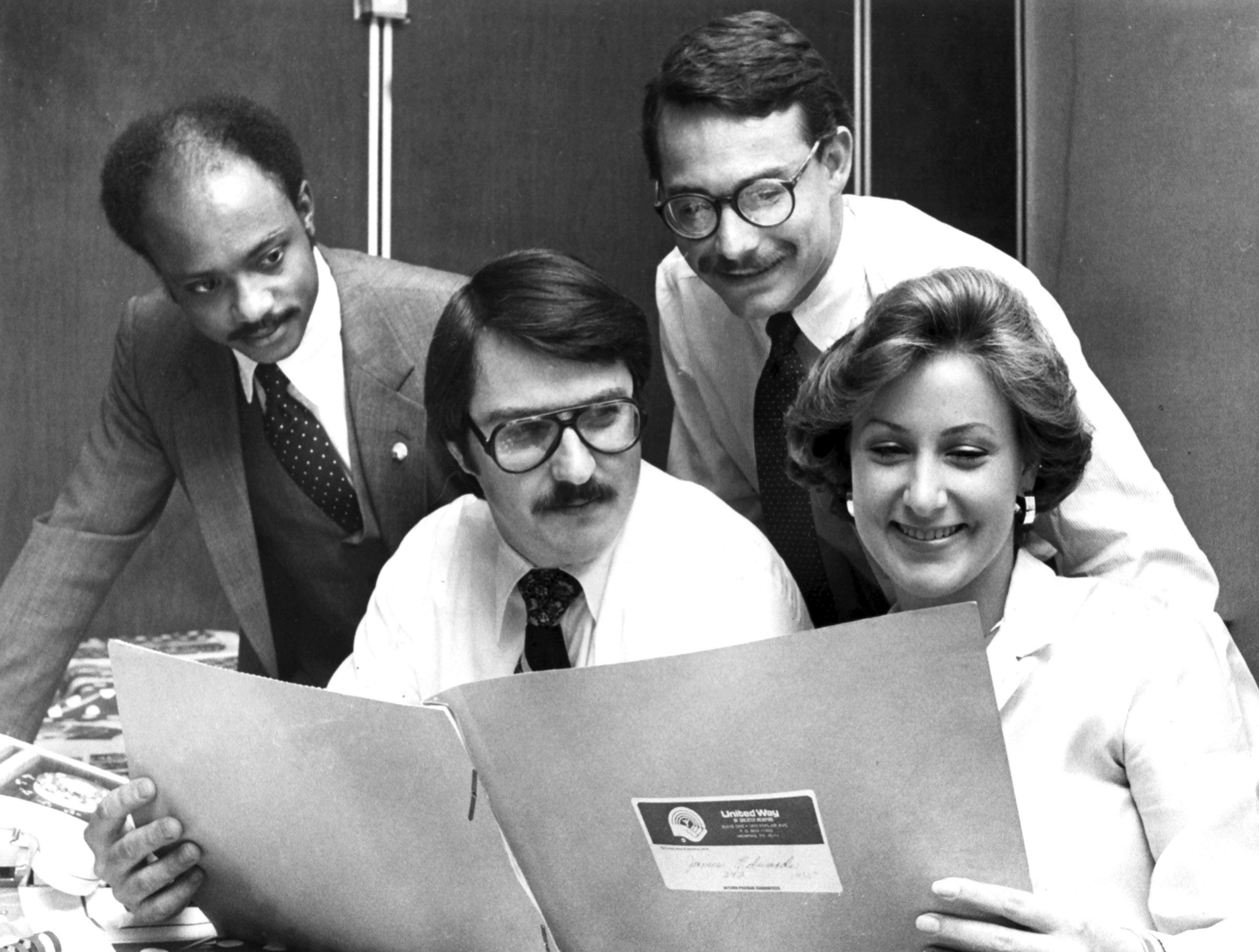 """Michael Reed (From Left), Henry George, Clark Higgs and Ginger Whitsitt look over materials for United Way Fund """"loaned executives"""" as they prepare to help the organization with its annual fund-raising campaign on 18 Oct 1979."""