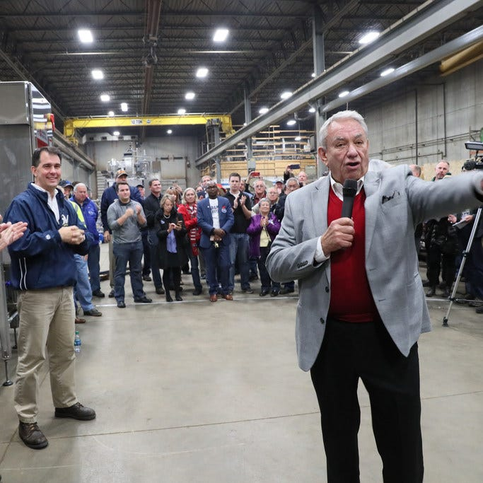 Former Gov. Tommy Thompson (front right) speaks at a rally for Gov. Scott Walker (left rear) at Pro Engineering and Manufacturing in Milwaukee.