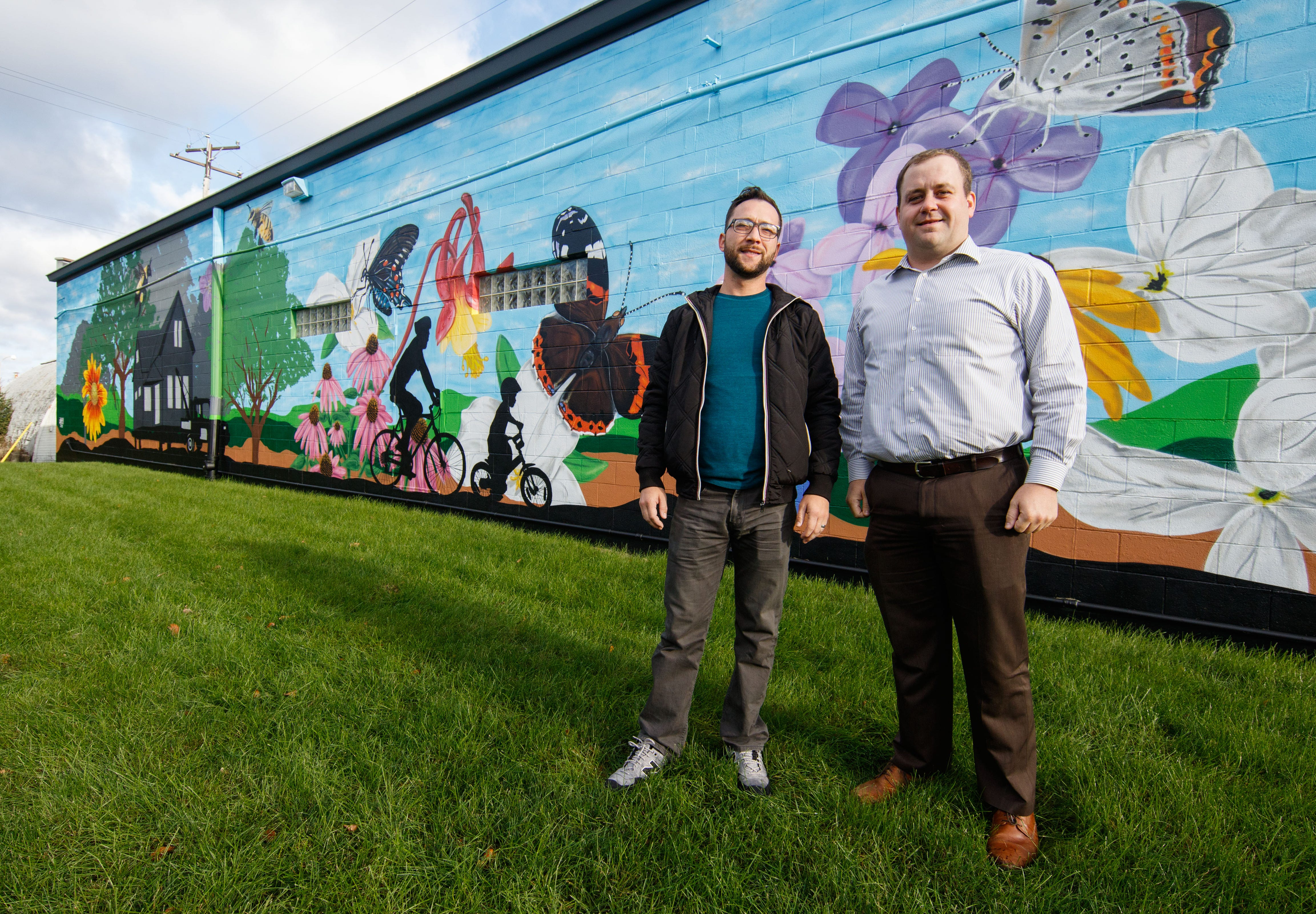 Local artist Fred Kaems (left) and General Manager Adam Nelson of Kelmann Restoration stand in front of the mural Kaems painted on the south side of the Kelmann Restoration building on Monday, Oct. 15. The mural faces the Hank Aaron Trail near 121st Street in Wauwatosa.