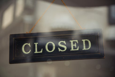 A close up of a 'CLOSED' sign hanging in a window