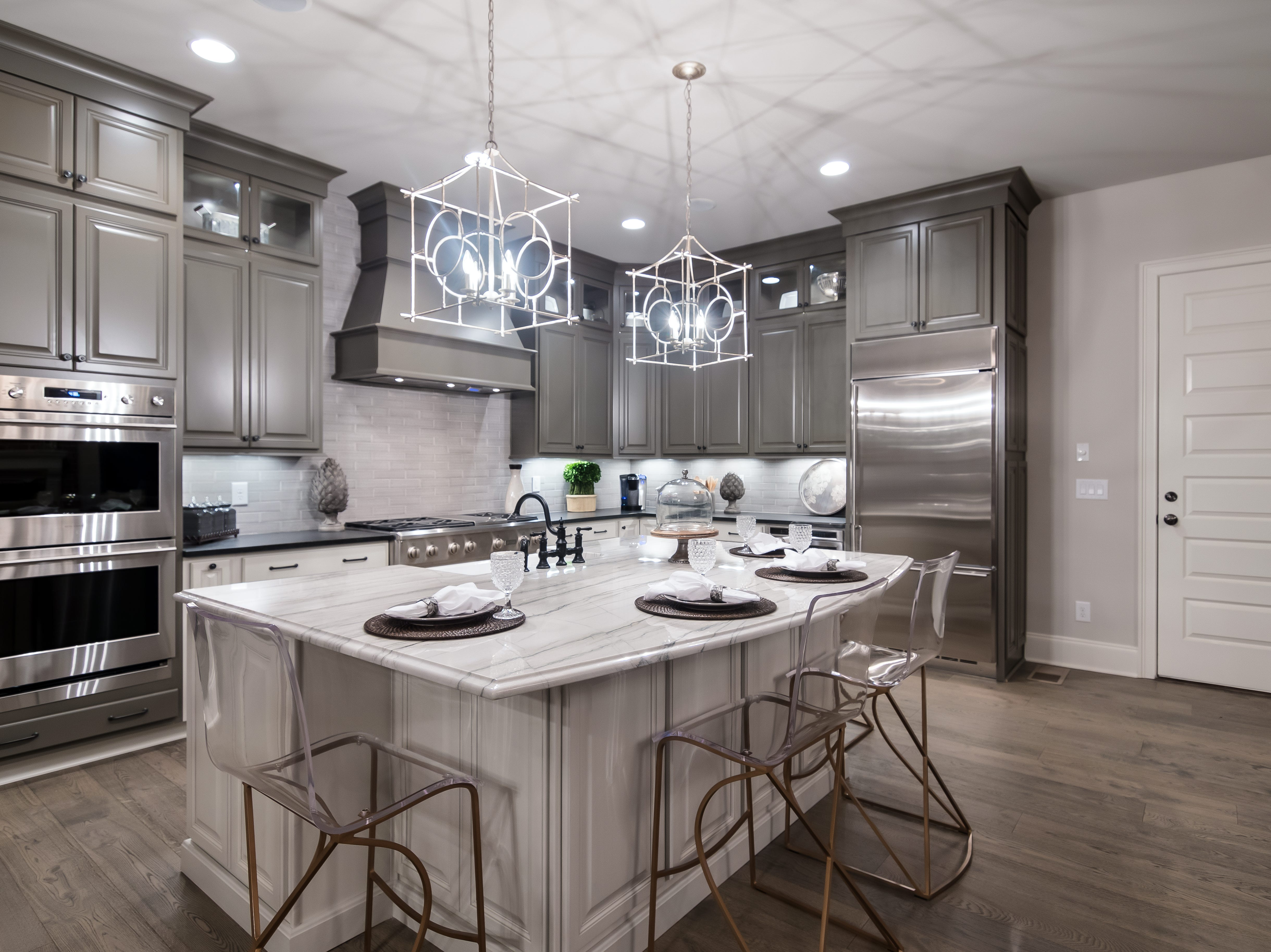 The kitchen in the Lookaway Farms model home also showcases some of the upgrades that come with the home such as painted cabinets and higher-end finishes such as the pendant lights.