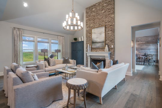 The living room of the Lookaway Farms model features a floor-to-ceiling brick fireplace.