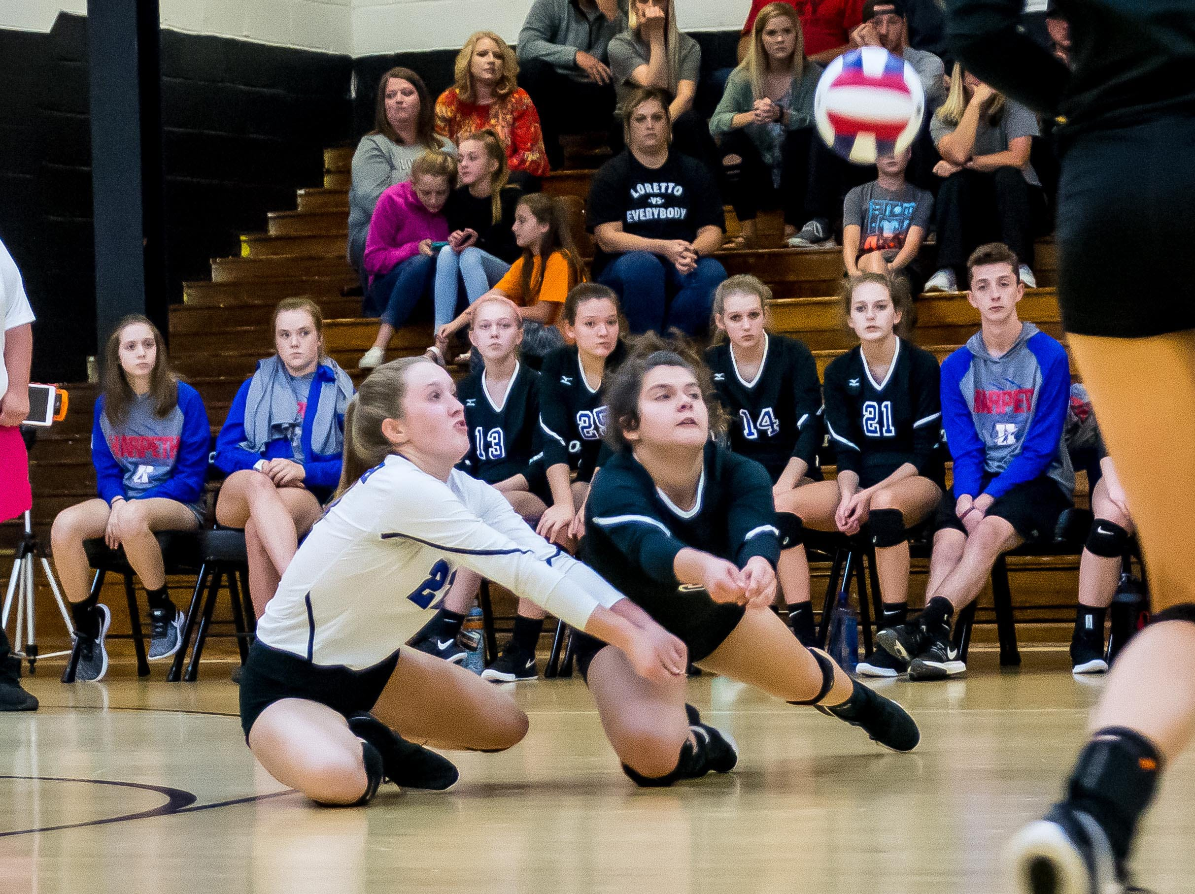 Addison Beshears and Katie Rogers dig up a shot against Loretto.
