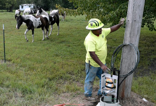Steven Bacheco with Ben Lomand Connect helps install equipment for high speed internet cable in the rural Pocahontas area in northern Coffee County on Aug. 22.