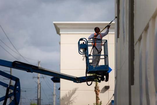 A worker paints one of the Naples Motor Condos being built Wednesday, October 10, 2018, on Livingston Road in East Naples.