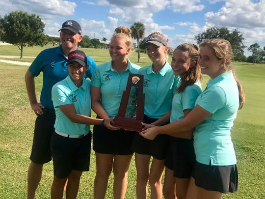Gulf Coast High School girls golf coach Justin Ahasic, left, and players Kylie Mani, Sierra Studer, Megan Ariza, Mackenzie Meador and Maggie Platten pose with the Class 3A-District 15 trophy after shooting a 347 at St. Andrews South Golf Club in Punta Gorda on Monday.