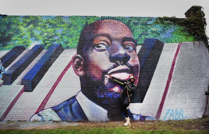 Rapper Wyclef Jean poses for photos as he leans on the mural of himself painted by Englewood artist Camille Cote, during an official ceremony in Newark held by Grammy Museum Experience Prudential Center on 10/15/18.