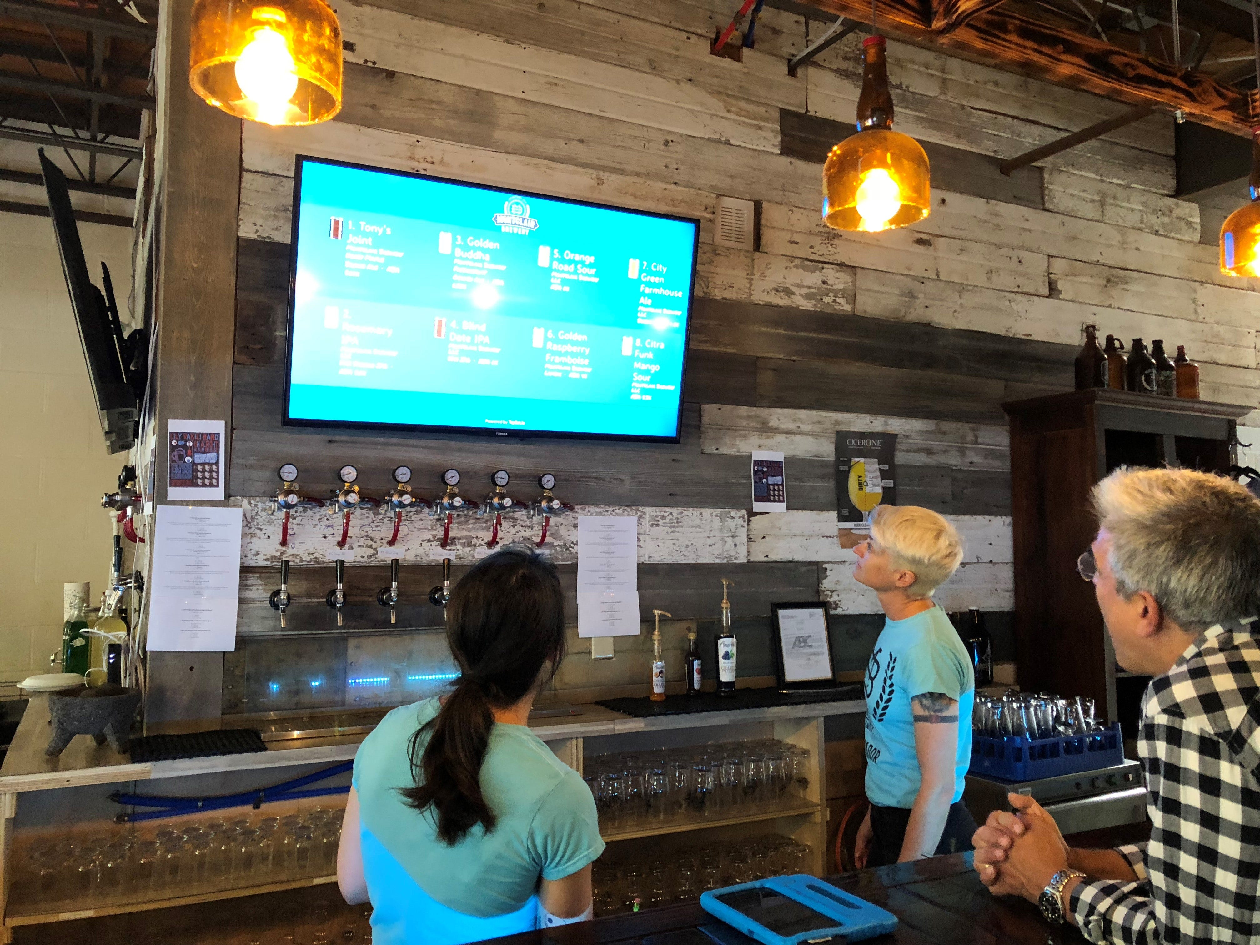 A screen displays the offerings on tap at Montclair Brewery.