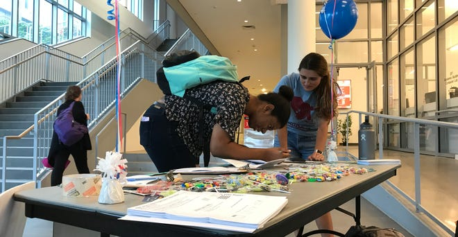 NJPIRG's Rutgers-New Brunswick campus organizer, Arielle Mizrahi, helps a student fill out a voter registration form on Oct. 11, 2018.