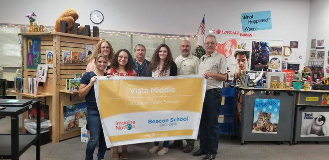 From left, Vista Middle School math teachers Heather Nevarez, Staci Pedersen, Alexis Puente, Robert Gallegos, Perla Trujillo, Principal Mike Brewer and math teacher Theron Imlay pose with a banner from Imagine Nation recognizing Vista Middle School as a Beacon School.