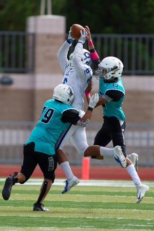 Carlsbad's Trey Castaneda (6) makes a catch between two Oñate defenders during Saturday's game.