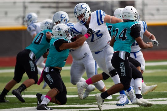 Carlsbad's Taylor Miterko (75) is held by an Oñate defender as he tries to sack the quarterback during Saturday's game.