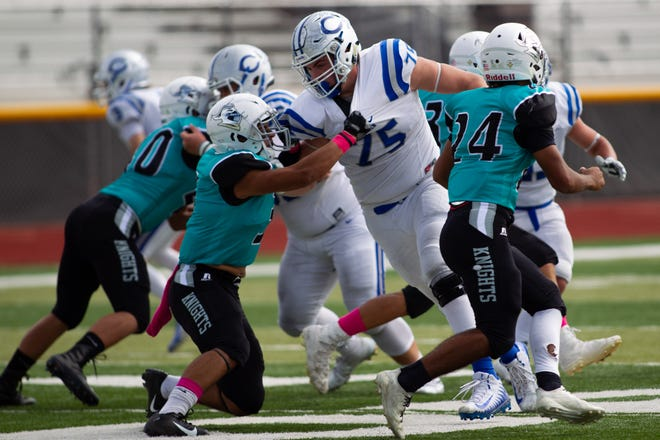Carlsbad's Taylor Miterko (75) is held by an Oñate defender as he tries to sack the quarterback.