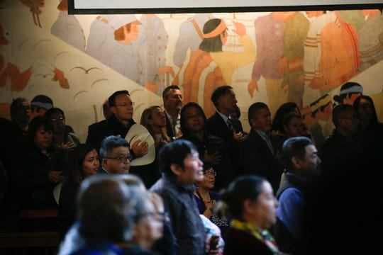 Community members and guest join Navajo Nation Council Delegates in the singing of the National Anthem Monday at the Navajo Nation Council Chamber in Window Rock, Arizona.
