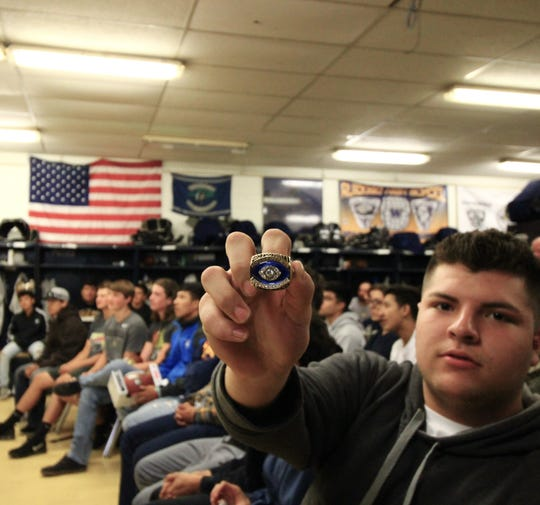 A football player of the Ruidoso High School Warriors team proudly shows off Hall of Fame Jim Kelly's pro ball ring with honor and pride.