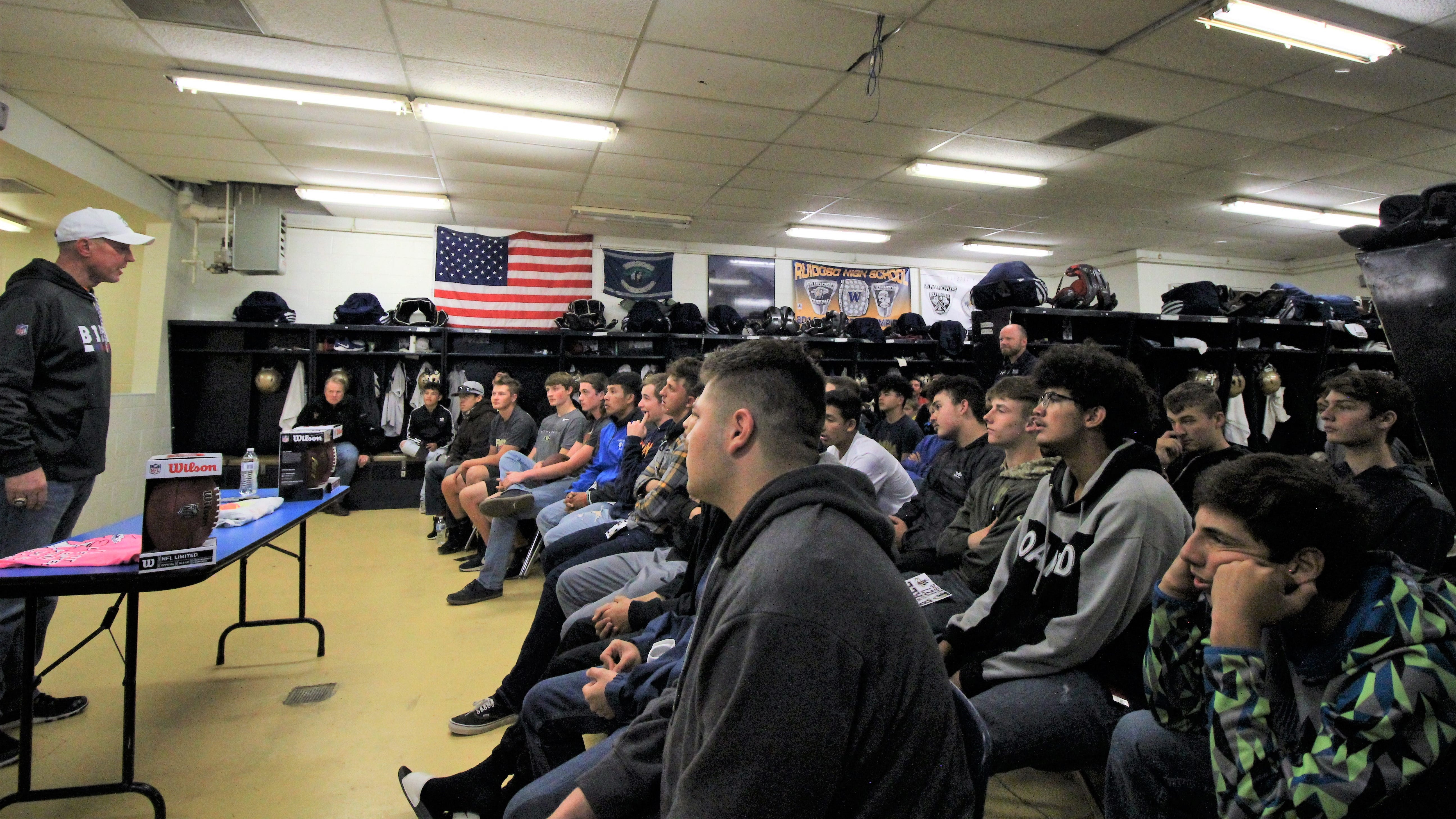 The Ruidoso Warriors and guests listen carefully to Hall of Fame Quarter Back Jim Kelly from the Buffalo Bills as he speaks about staying positive no matter what may happen in life.