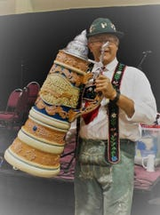 A man in traditional German dress holds up a beer stein during Oktoberfest