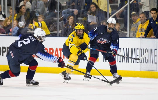 Josh Norris (14) of the Michigan Wolverines tries to split U.S. NTDP Under-18 players Cam York (2) and Trevor Zegras (11) during the Oct. 12 game at Yost Ice Arena. Norris (Oxford, Mich.) is a NTDP alum.
