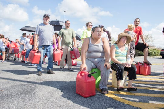 Ashley Le, center, and her mother Diane Le wait in a 3-hour-long line for gas in the Calloway Walmart parking lot in Panama City, Florida on Monday, October 15, 2018.  The Le family lost part of their roof on the second floor during Hurricane Michael, but remain in the lower floor of their house in Calloway.  Non-profit Fuel Relief Refund is giving away 5 gallons of gas per person until their fuel truck runs out.