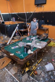 Owner Tony Barr checks out the damage to his Bare Naked Vapors LLC vape shop after Hurricane Michael in Panama City, Florida on Monday, October 15, 2018.  His friend Bobbie Amaya survived the storm by taking refuge in the bathroom of this store.
