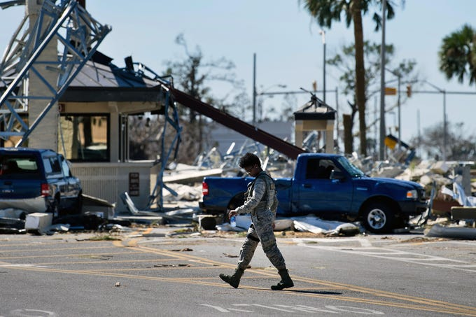 A military police officer walks near a destroyed gate in Tyndall Air Force Base, in Florida in the aftermath of Hurricane Michael on October 12, 2018 . - Rescue teams using sniffer dogs carried out a grim search for victims of Hurricane Michael on Friday amid fears that the death toll from the monster storm, which currently stands at 11, could rise.