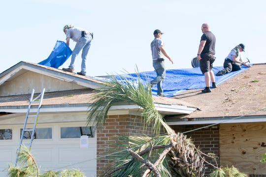 A group of people tarp a roof Monday in a Callaway neighborhood after Hurricane Michael in Panama City.