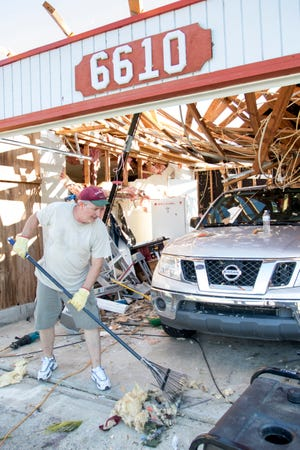 Rick Gaddy rakes debris from his garage after Hurricane Michael in Panama City, Florida on Monday, October 15, 2018.