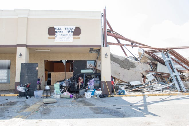 Bobbie Amaya, who lost her mobile home during Hurricane Michael, camps in her minivan outside of her friend's vape shop along 15th Street in Panama City, Florida on Monday, October 15, 2018.  Amaya and her son survived the storm inside the vape shop, but the unit next door totally collapsed and damaged her vehicle that was parked in front of the door.