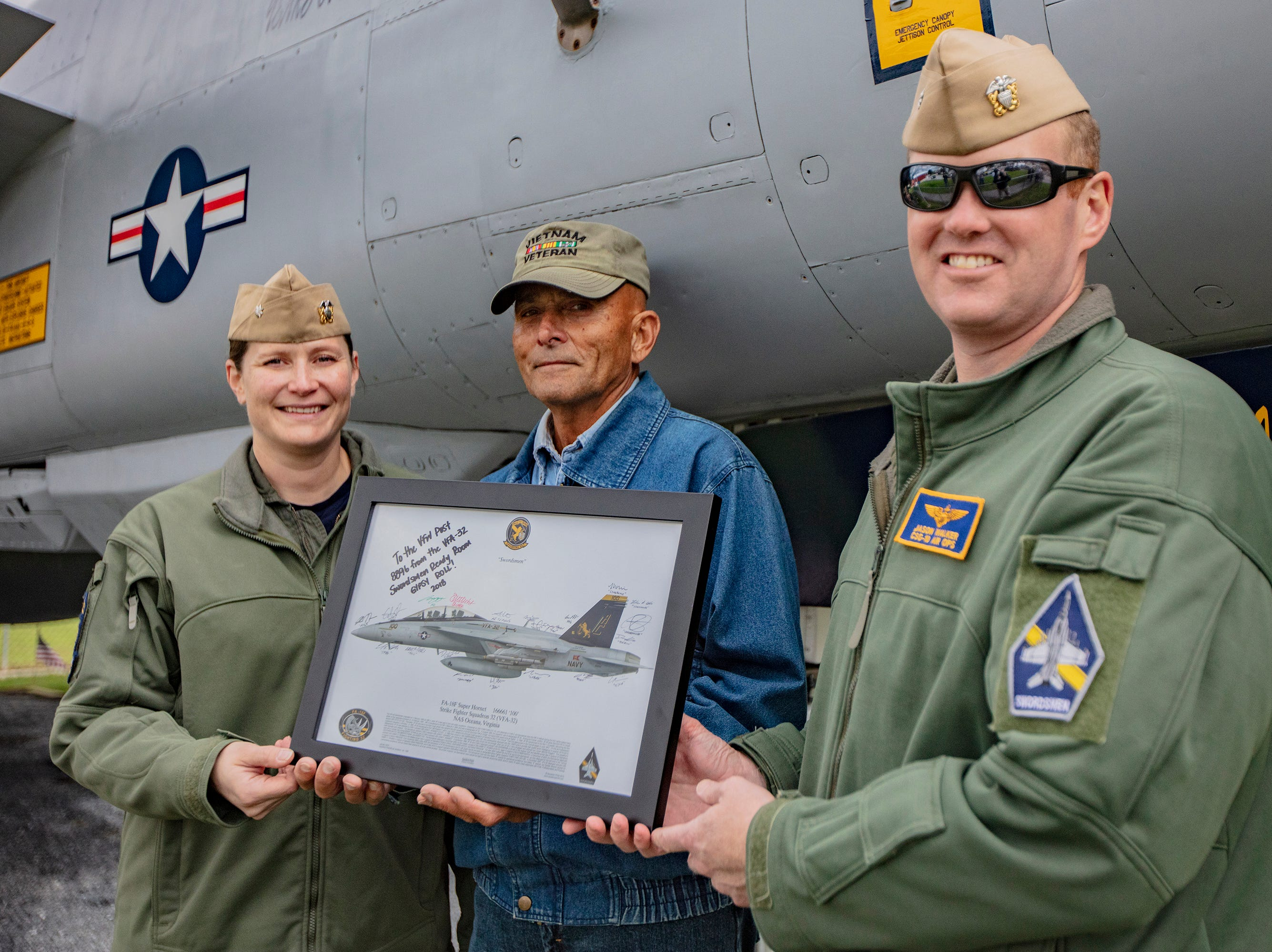 "Cdr. Stacey L. Uttecht, Squadron Commanding Officer, VFW Member and ""Keeper of the Cat"" Gary L. Kopp, and Cdr. Jason D. Walker, CSG 10 Air Operations Officer, present a signed lithograph of the Tomcat from the squadron to the East Berlin VFW on  Saturday, Oct. 13, 2018."