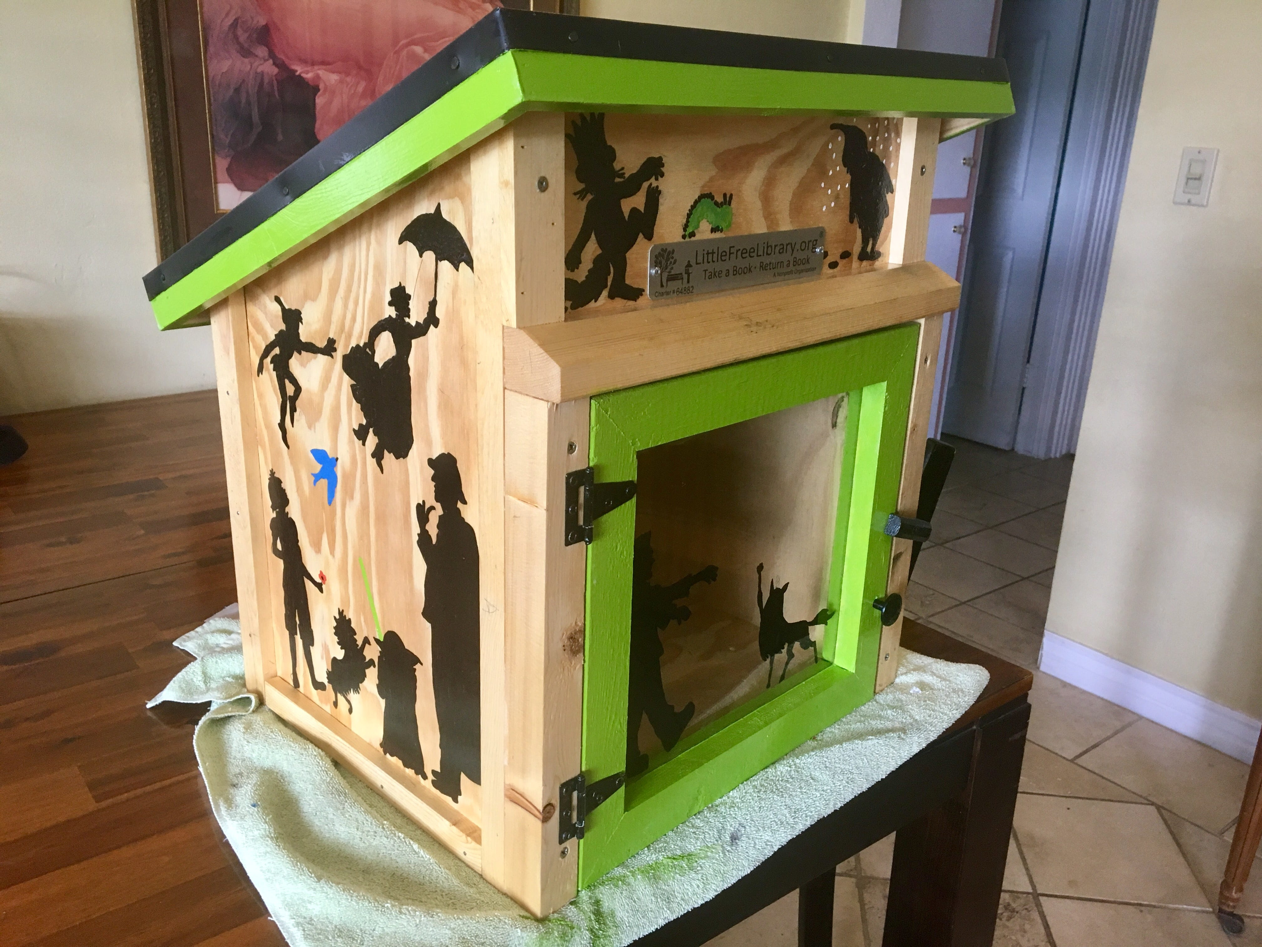 With a few days off, Karina Bland painted theL ittle Free Library with silhouettes of book characters and edged it in bright green.