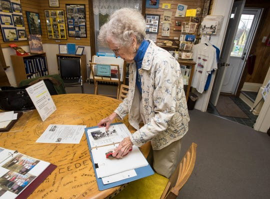 Joan Bulley, 88, looks through photographs that were stored in a notebook Monday, Oct. 15, 2018 at the Algonac Clay Historical Museum.