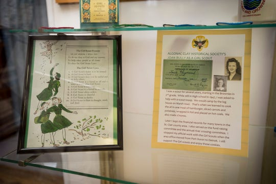 The Girl Scout Promise sits in a frame next to an article about Joan Bulley (Raymond) as a Girl Scout in a display case at the Algonac Clay Historical Museum.