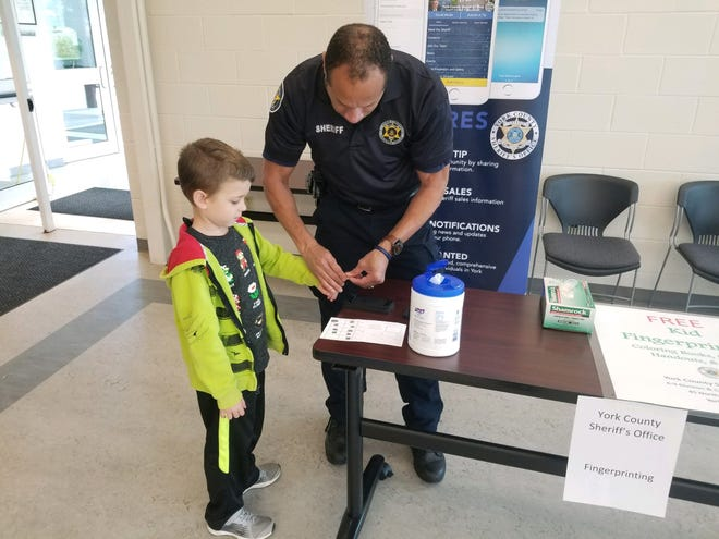 Grant Runshaw, of Manchester Borough, learns about fingerprinting with a lesson from Deputy Michael Reese during the 911 Center's open house Saturday, Oct. 13.