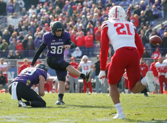 Northwestern's Drew Luckenbaugh, center, kicks his game-winning field goal in overtime from the hold of Jake Collins, left, as Nebraska's Lamar Jackson looks on during an NCAA college football game Saturday, Oct. 13, 2018, in Evanston, Ill. (AP Photo/Jim Young)