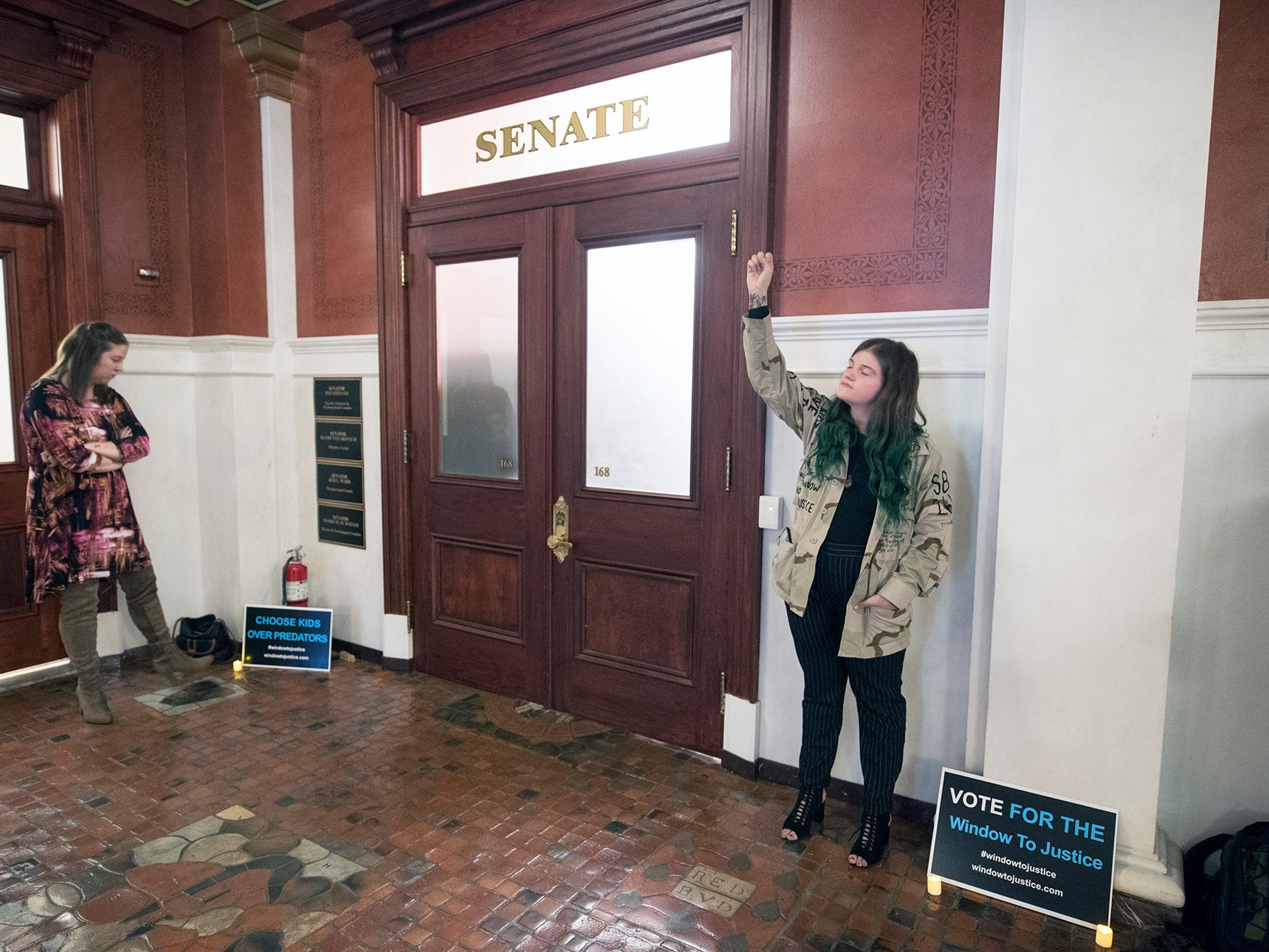 Taylor Ecker, right, stands at the doors of the Senate chamber reciting statistics of sexual abuse during the demonstration for statute of limitations reform to the state's childhood sexual abuse laws at the state capitol in Harrisburg Monday October, 15, 2018. Becca Velner, at left, was a victim of non-clergy sexual abuse.