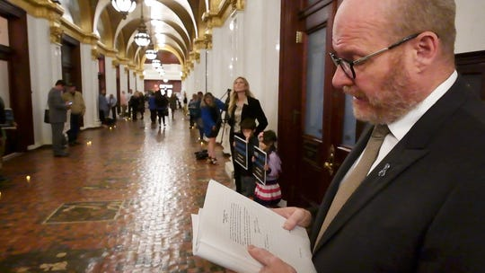 Shaun Dougherty, a survivor of clergy abuse, reads an excerpt from the state grand jury report during the demonstration for statute of limitations reform to the state's childhood sexual abuse laws at the state capitol in Harrisburg on Monday.