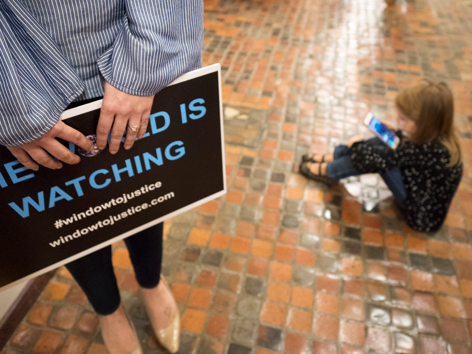 Adrienne Doolan, left, holds a sign while her daughter Reagan sits close by during the demonstration for statute of limitations reform to the state's childhood sexual abuse laws at the state capitol in Harrisburg Monday October, 15, 2018.
