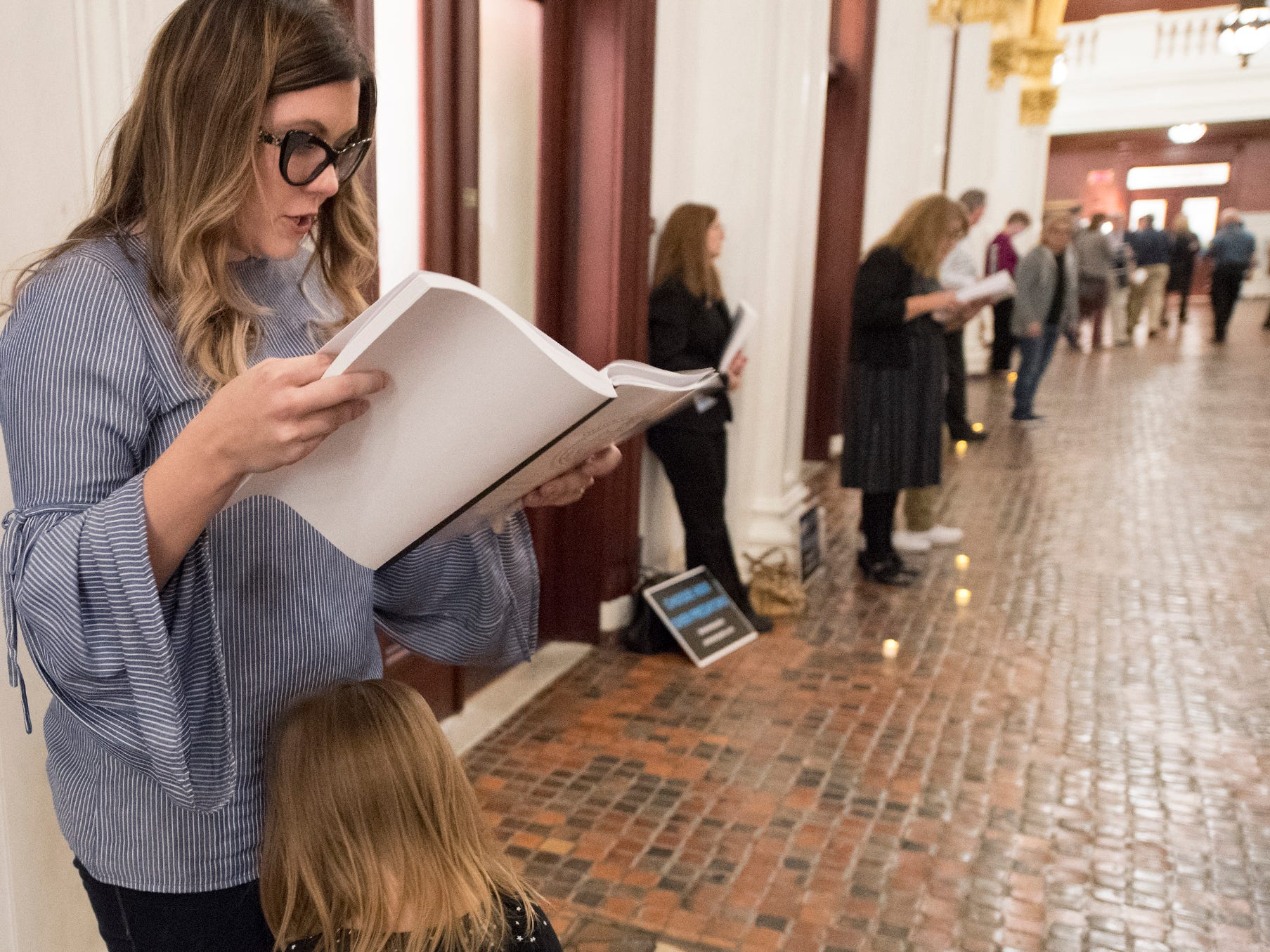 Adrienne Doolan, top, a victim of non-clergy sexual abuse in Hanover, reads excerpts aloud from a state grand jury report while her daughter Reagan, 4, leans into her during the demonstration for statute of limitations reform to the state's childhood sexual abuse laws at the state capitol in Harrisburg on Monday. Doolan said that she wanted her daughter to understand that she should speak up immediately if someone harmed her.
