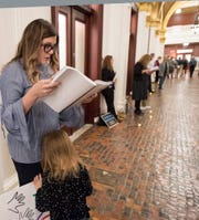 Adrienne Doolan, top, a victim of non-clergy sexual abuse in Hanover, reads excerpts aloud from a state grand jury report while her daughter leans into her during a 2018 demonstration for statute of limitations reform in Harrisburg.