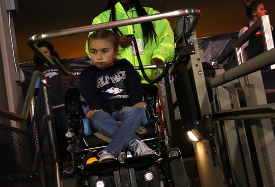 Ella Marini, 7, gets loaded onto a special lift as she makes her way into Mackay Stadium to see Nevada take on Boise St. in Reno on Oct. 13, 2018.