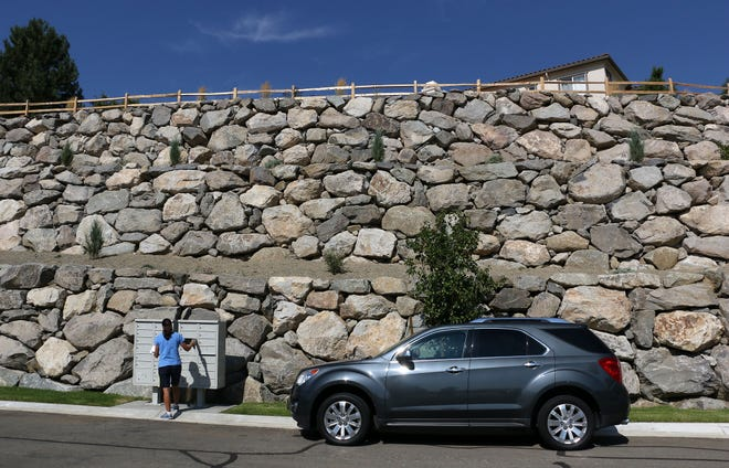 A resident gets her mail below a huge rock wall in the Somersett master planned community in Reno on Aug. 29, 2018.