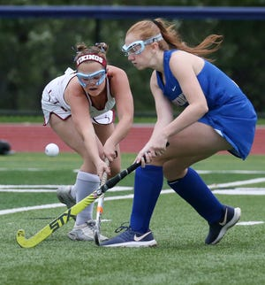 Mendon's Anya Lucey, left, battles for a loose ball with Schroeder's Madeleine Kaptein during their Section V field hockey matchup.
