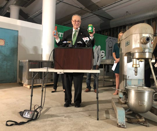 U.S. Senator Charles Schumer holds products that aspiring Rochester entrepreneurs hope to produce at The Commissary Downtown Kitchen Incubator.