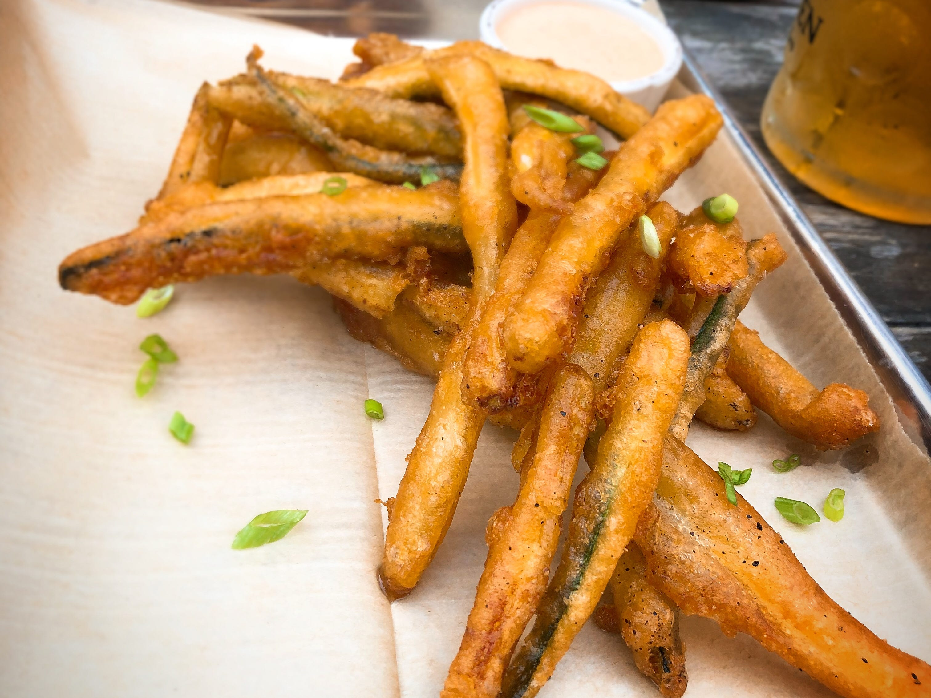 Beer-battered zucchini fries  are light and airy. At top is the giant pretzel by Amazing Grains Bread Co.