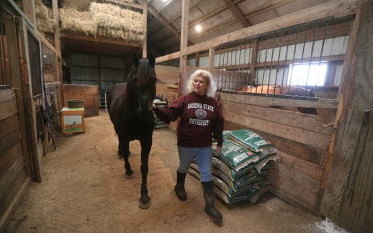 Karin Stroh, in the six-stall barn that is part of the property she and her husband are selling in Ogden.